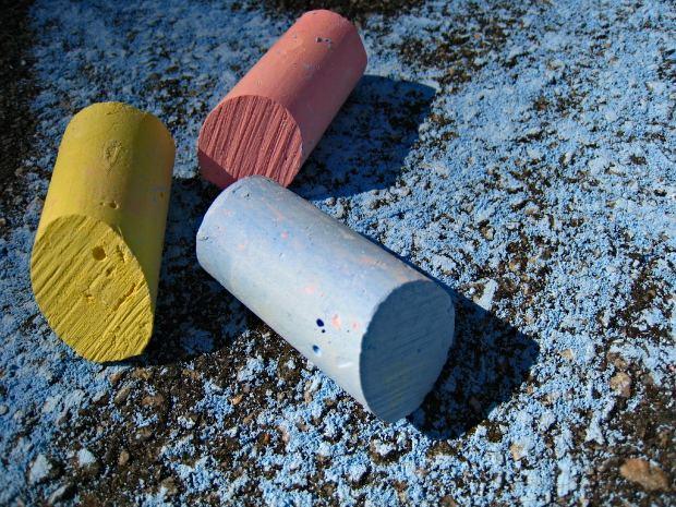 Pieces of used sidewalk chalk on street.