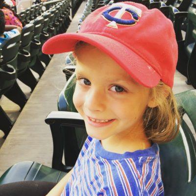girl with Minnesota Twins hat at baseball game