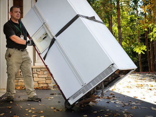 Man moving old refrigerator on a dolly