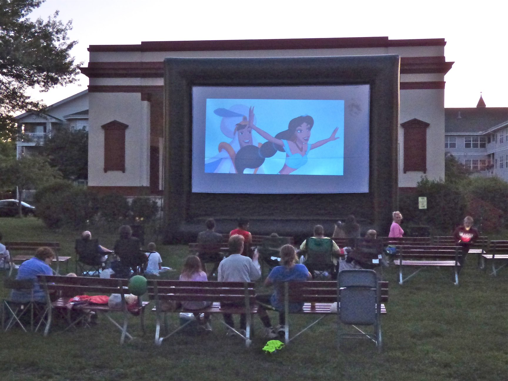 people watching Aladdin in park on large movie screen