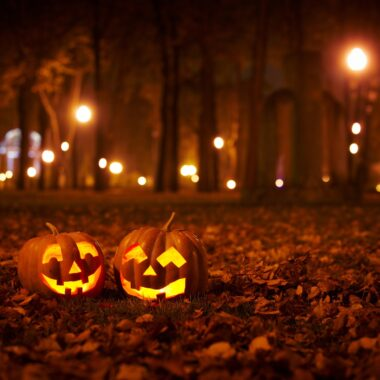 two carved jack-o-lanterns in field at night