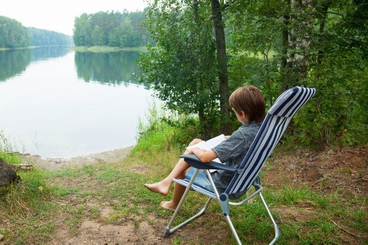 CHILD READING BY MINNESOTA LAKE
