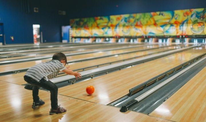 child bowling with orange bowling ball