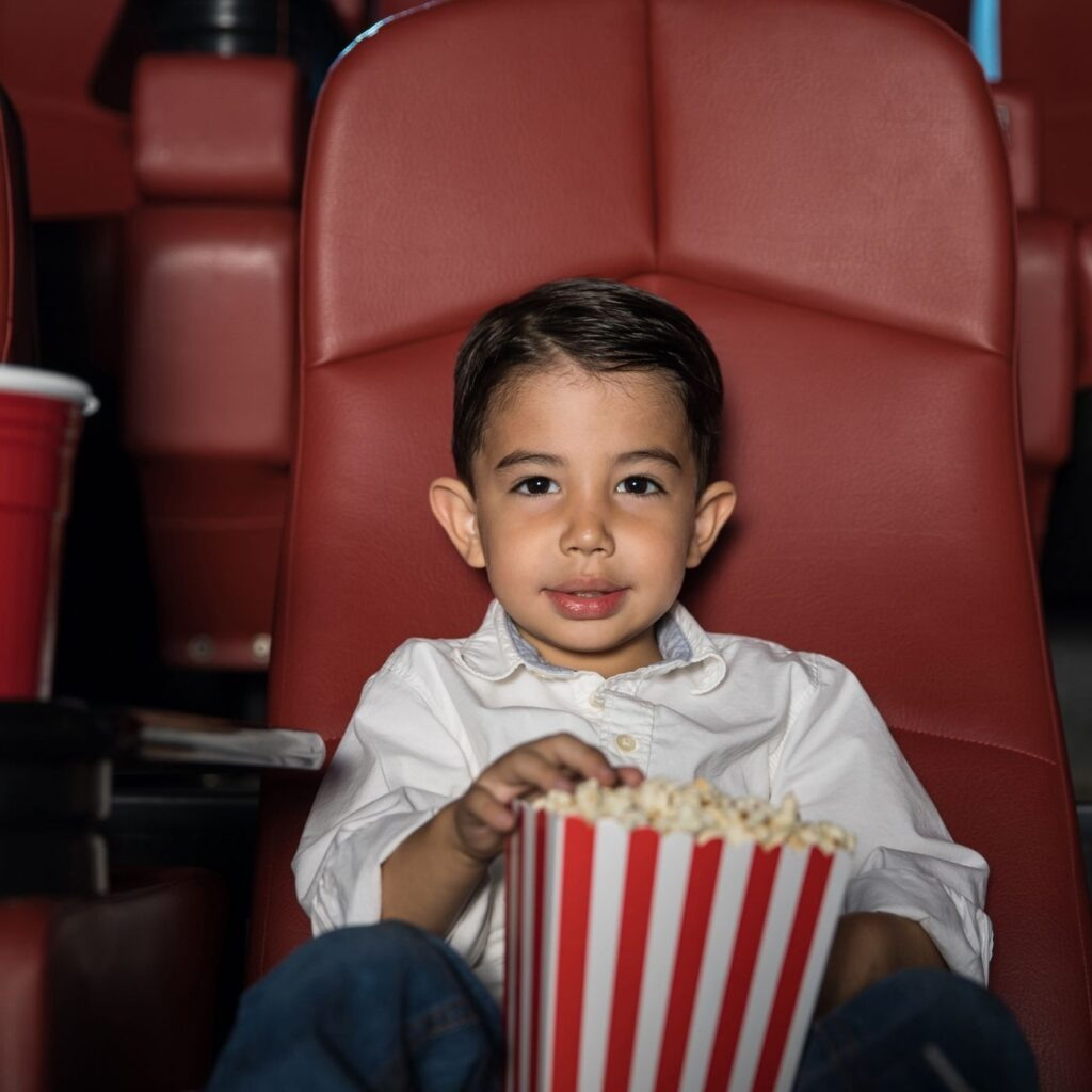 little boy in movie theater with popcorn
