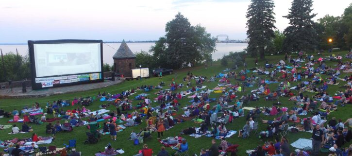 crowd seated on hill on grass watching outdoor movie
