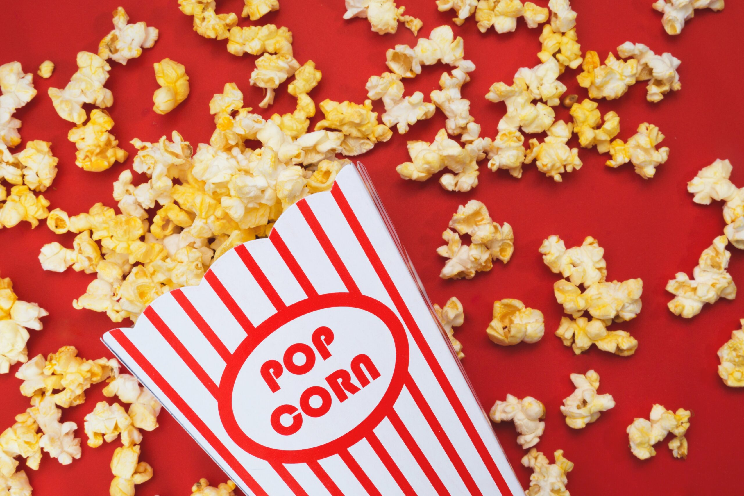 movie popcorn in striped box with popcorn spilling onto red background